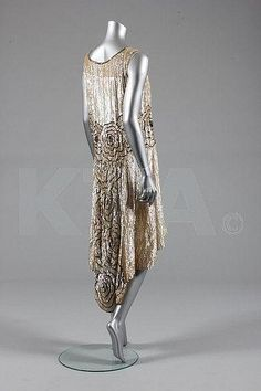 Description:  A sequined flapper dress, French, circa 1928, the ivory muslin ground adorned with pearlescent and gold sequins, the waist and skirt adorned with large flowerheads, trained...Back