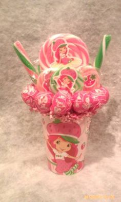 One made to order Strawberry Shortcake Lollipop Bouquet. An adorable gift idea for someone young or old or great table centerpieces for your Strawberry Shortcake Theme Birthday Party.  **Cup is reusable** **Lollipops are all edible and YUMMY**