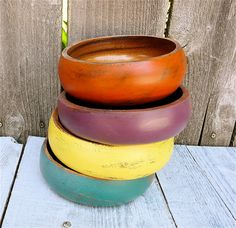 Four gorgeous solid wooden bowls now have a beautiful new lease on life. They have each been painted in a coordinating color, sanded down and