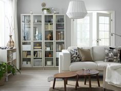 A small living room furnished with a light beige two-seat sofa and two beige glass door cabinets filled with books, treasures and sentimental items.