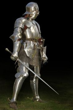 Medieval knight in shining armour of the 15th century standing outside with sword. Isolated on a dark background  Stock Photo