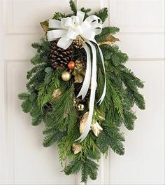 Brighten any door or window with this attractive traditional Swag crafted from faux Cedar and White Pine boughs. Designed by Sevens Sisters Florist www.sevensistersflorist.com