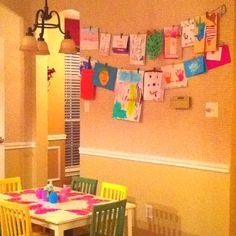 Fun, easy way to display my kid's school work! Yarn fixed with a single staple on each end, and miniature clothes pins to hold any size creation.