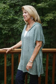 This poncho is knit in one piece from the bottom front to bottom back with instructions for front tab and neck opening along the way. Stitches are later picked up at the neck opening for the hood. The top of the hood is finished with Kitchener stitch. Braided ties are added at the neckline edge and poncho sides are partially joined by tacking together several inches in from the side edge.