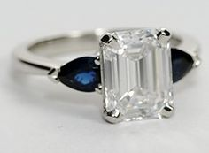 Two beautifully matched pear-shaped blue sapphires, prong-set in platinum, offer the perfect contrast to your choice of center diamond.