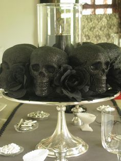 place black skulls and roses on a cake platter with a black candle in the middle for a creepily elegant halloween centerpiece