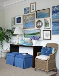 Cool coastal gallery wall paired with a wicker accent chair and blue skirted storage ottomans.