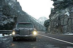 classic sedan 250SE, head lights, grey rocks, winter road, white line
