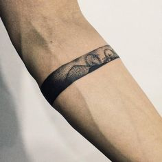 Arm band tattoo of an amusement park on the left forearm.