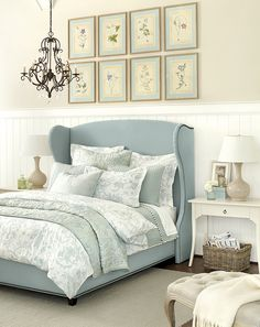 Blue bed, white side tables, white wainscoting, tan wall, chandelier