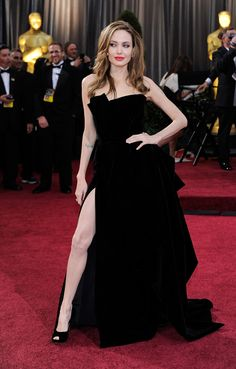 Angelina Jolie, 2012 Although it was overshadowed by her much-meme'd right leg, Jolie's dress itself deserves a nod. The black velvet strapless Atelier Versace gown was classic Hollywood glamour with a sexy twist—that thigh-high slit, of course. Oscar Gowns, Best Oscar Dresses, Iconic Dresses, Oscar Verleihung, Oscar Fashion, Fashion Mode, Celebrity Red Carpet, Celebrity Dresses, Celebrity Style