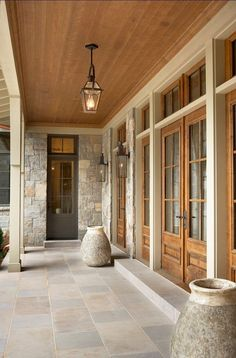 Beautiful Lake House - Indiana Limestone porch flooring with stained wood doors, transom windows and ceiling - via Home Bunch Exterior Design, Interior And Exterior, Interior Doors, Stone Interior, Exterior Colors, Wood French Doors Exterior, Stone Exterior Houses, Ranch Exterior, Exterior Shutters