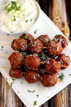 Spicy sausage meatballs spiked with Red Moscato wine, these Moscato Meatball Skewers are served alongside a cool yogurt sauce for a perfect appetizer or main course.