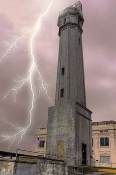 Alcatraz Lighthouse on Alcatraz Island, San Francisco Bay, with an appropriate streak of lightning. This lighthouse is about as bleak as the prison. San Francisco, Fuerza Natural, Jolie Photo, Abandoned Places, Places To See, Beautiful Places, Around The Worlds, Island, City