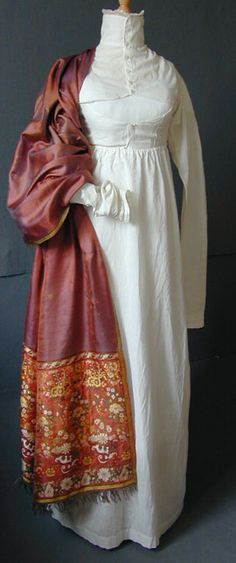 High-necked white cotton sport under gown, English, c. 1800. This would have been worn under a heavier dress, redingote or a riding habit, when a high neck would be needed. The cutaway front would have allowed flexibility while moving the arms, playing archery, or other country pursuits. The gap front would also mean that the front would not ride up but would remain neat in place under the outer bodice. The buttoning is masculine, left over right, indicating this was worn for outside…