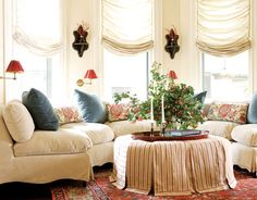The relaxed charm of the sitting room proves designer Alessandra Branca's theory that the best luxury is comfort. Plumping up the bay window, a banquette she designed is covered in Gretchen Bellinger linen velvet; the custom ottoman is casually draped in Rogers & Goffigon striped ticking. And the floral linen and blue velvet add just the right amount of romance.