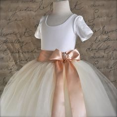 A romantic length tutu created in full layers of ivory tulle that is sashed with a blush satin luxury ribbon sewn to the natural waist. The bow