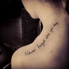 """The title itself sums it up pretty good for this tattoo. It's a quote tattoo on a girl's back/shoulder saying: """"Never Forget Who Your Are""""."""