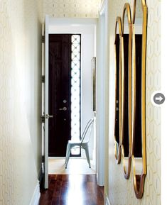 """Narrow Hallway: Homeowner and designer Yanic Simard used to call the dark three-by-20-foot hallway """"the tunnel."""" He brightened it up by adding graphic wallpaper, lighting that illuminates both up and down, and a row of mirrors, which reflect light and visually widen the space."""