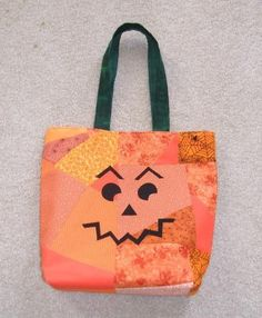 Warm patchwork in oranges, gold, and yellow fabrics, creates a spooky tote bag designed by Celestial Inspirations especially for witches and ghosts to hold their loot on Halloween night. A differen...