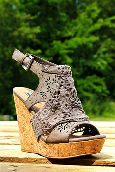 Our The Candace Wedge - Taupe is seriously the most adorable wedge! It has laser cut designs on the front with a lace overlay to accent. Cork wedge with a buckle fasten.