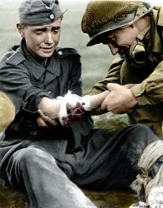 A young German soldier in pain being treated by American GI.