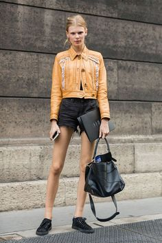 A orange leather cropped jacket is worn with high-waisted black shorts, a black bag and black shoes.