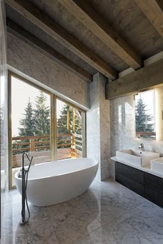 Victor Hugo Combloux. Luxury freestanding oval bath overlooking beautiful views. Wood and marble are a great combination with the matt white finish of the bath
