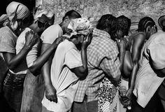 Riccardo Venturi, Contrasto - Port Au Prince, Haiti, 2010. Sfollati del terremoto in fila per la distribuzione di cibo si coprono il volto per l'imbarazzo.