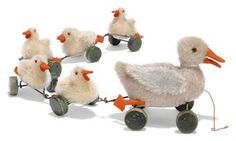 A STEIFF MOHAIR DUCK CHAIN, (6310,2ex and 6306ex), grey mother, black glass eyes, red felt behind, orange felt beak and feet, on green wooden eccentric wheels and FF button --6in. (15cm.) long; and five ducklings, yellow mohair, black bead eyes, red felt behind, orange felt beak and feet, green wooden eccentric wheels and three FF buttons, circa 1930 --3¼in. (8.5cm.) long (some thinning and fading)