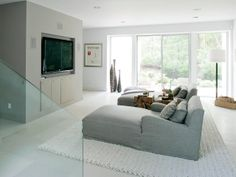 TV Room in the master suite in a modern farmhouse with a huge wall mounted tv, two long arm chairs, a white rug and a sliding door leading t...