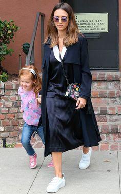 Jessica Alba com a filha usa look com vestido azul marinho com risca de giz, casaco sobretudo azul marinho, óculos gatinho, bolsa com patches e tênis branco