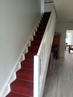 Ein roter Treppenläufer auf weißer Treppe wirkt edel und lädt freundlich ein das Dachgeschoss zu betreten.