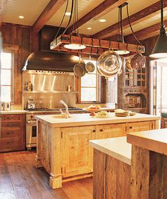 i like the galvanized shelves behind the stove and the high vent hood, and the giant pot rack with the beamed ceiling