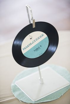 Record table marker with custom designed labels for wedding table numbers. Music and fashion inspired wedding.