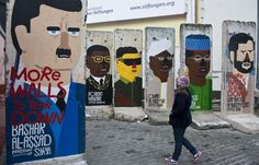 A girl looks at concrete slabs from the former Berlin wall decorated with likenesses of (from R) Iranian President Mahmoud Ahmadinejad , Chad's President Idriss Deby, Sudan's President Omar Al-Bashir, former North Korean leader Kim Jong-il, Zimbabwe's President Robert Mugabe, and Syrian President Bashar al-Assad, by French artist Guillaume Kashima, near the city's Checkpoint Charlie area in Berlin on January 13, 2013. (John MacDougall/AFP/Getty Images)