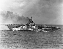 Essex class USS Ticonderoga (CV-14) lists to port in the aftermath of a kamikaze attack in which four suicide planes hit the ship, 21 Jan 1945. Note her camouflage scheme measure 33/10A and the Fletcher-class destroyer in the background.