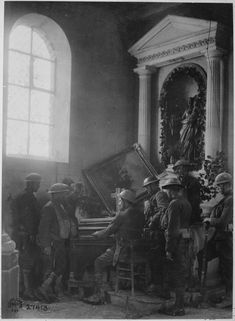 A squad of American soldiers listening to one of their comrades playing the organ in the half-wrecked old church in Exermont in the Argonne. France October 11 1918.