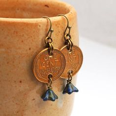 These fun coin earrings are made with US Wheat pennies from 1946 and 1958. Ive used antiqued brass earwires, brass colored enameled copper jump rings, and Ive wirewrapped glass flower beads to the bottom of each coin with antiqued brass headpins. The earrings measure 1 3/4 long