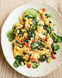 Scrambling eggs with vegetables and greens is a fast and easy way to prepare a nutritious breakfast. Stir in almost any sautéed vegetables that strike your fancy, such as the tomatoes and zucchini ...