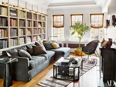 The living room in Nate Berkus and Jeremiah Brent's New York City apartment is modern and airy. Linen curtains line a wall of widows, while club chairs from the '60s are situated next to a brass cocktail table.
