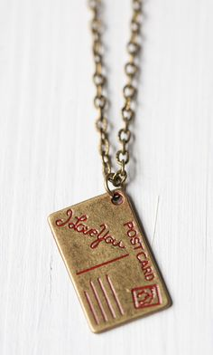 Postcard Charm Necklace | I believe this would be DIYable with a piece of clay, a nail for the text and lines and paint, a bit hard with all the small details but absolutely DIYable