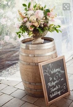 Barrel wine drums at end of aisle, adorned with flowers. Chalkboard welcome greeting sign. Baskets with fans for guests and programs.