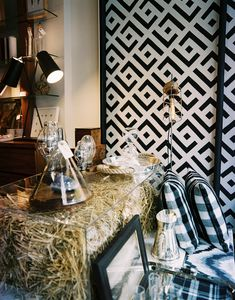 Rustic Retail Store Design - A transparent table filled with hay beside black-and-white patterned wall panels