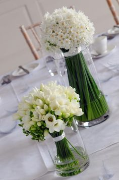 """these have gotta be really fragrant. i like how they pluralized narcissus.  flowers tied with ribbons look nice in the vases, too.     """"narcissi and freesia table arrangement."""""""