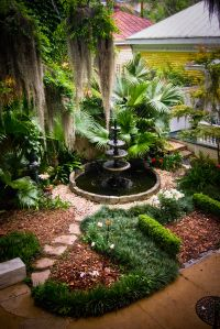 Tiered water feature is the focal point in this beautiful garden