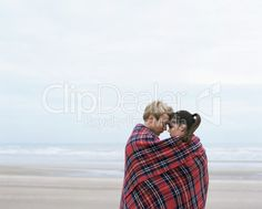 Couple on beach wrapped in blanket - royalty-free photo starting at $2.57