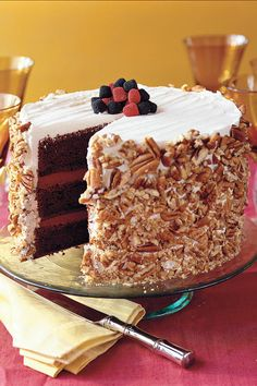 Blackberry-Raspberry Truffle Cake - Luscious Layer Cakes - Southernliving. Lavish amounts of semisweet chocolate and sour cream give rise to these luscious cake layers. No one will ever guess the recipe begins with a mix. A simple coating of coarsely chopped pecans and a handful of colorful berries will send this towering treat to the table in high style.  Recipe: Blackberry-Raspberry Truffle Cake