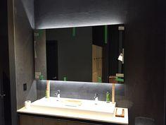 Stunning dark bathroom w/glowing LED lighting installed into mirror.