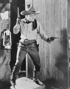 07f760b36a425 Tom Mix in Cowboy costume with guns in both hands.